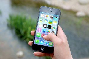 news, iPhone in der Hand mit Startbildschirm